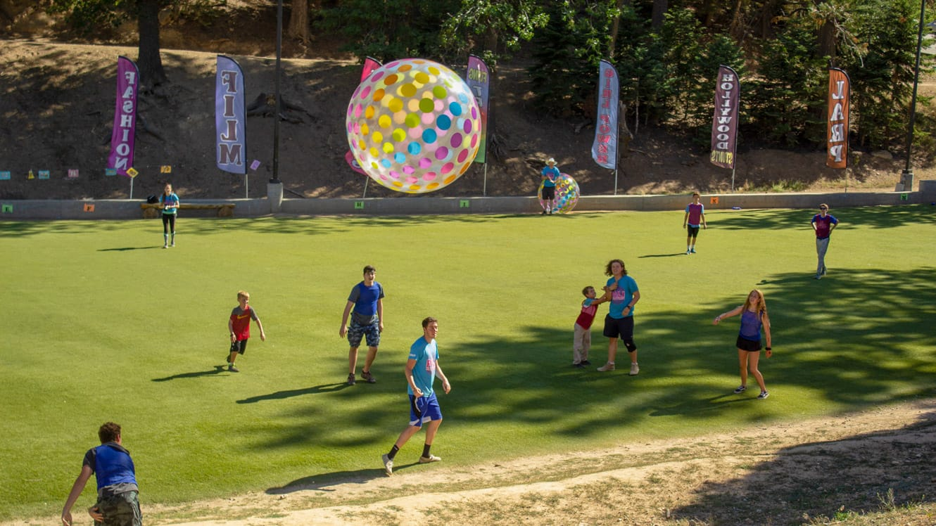 Campers on field playing with giant inflatable ball