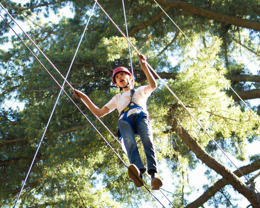 Boy walking on high ropes course wires