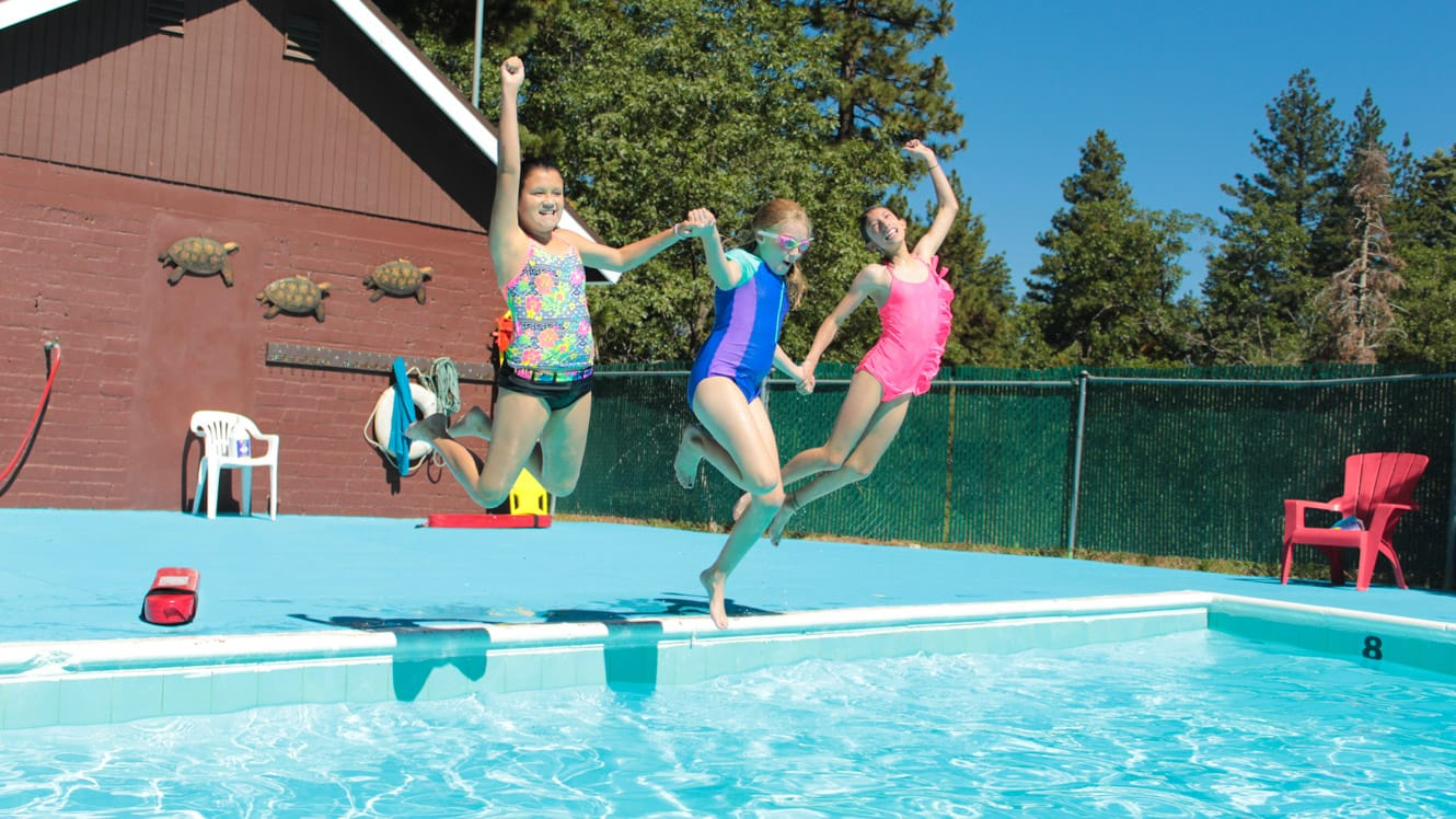 Three girls jumping into swimming pool