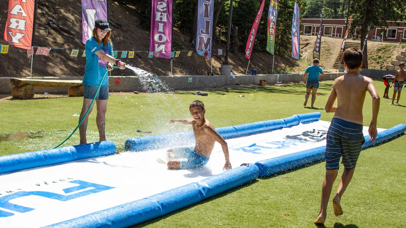 Campers and staff on slip n slide