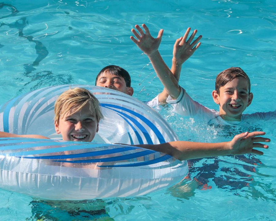 Three boys in swimming pool with tubes