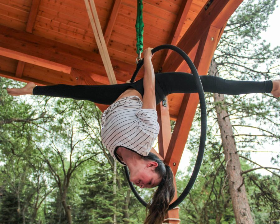 Girl on trapeze hoop upside down and doing a split