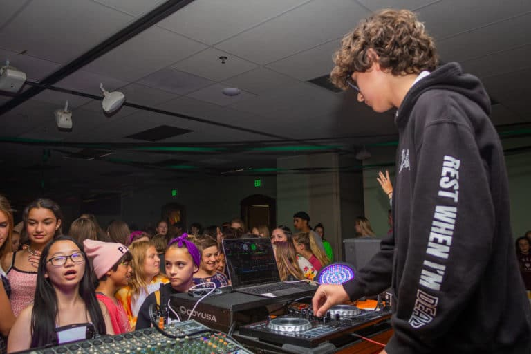 a kid in a dj booth while other kids dance