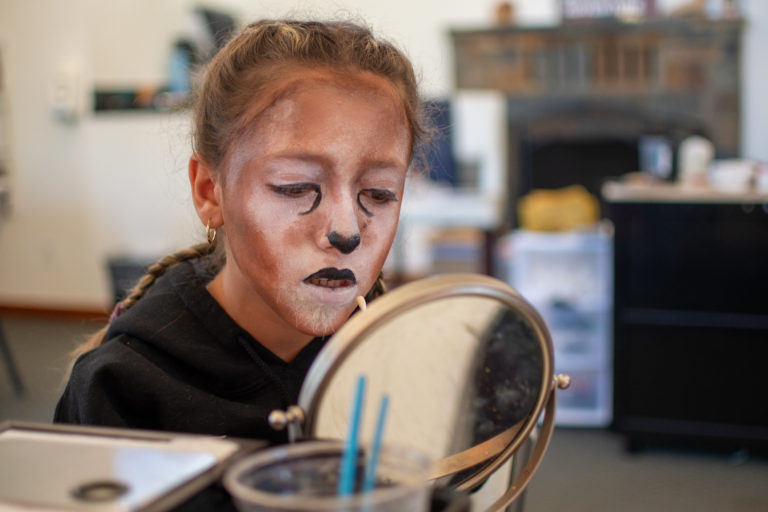 a girl painting her face to look like a cat