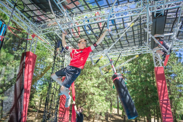 a boy swinging on an obstacle course