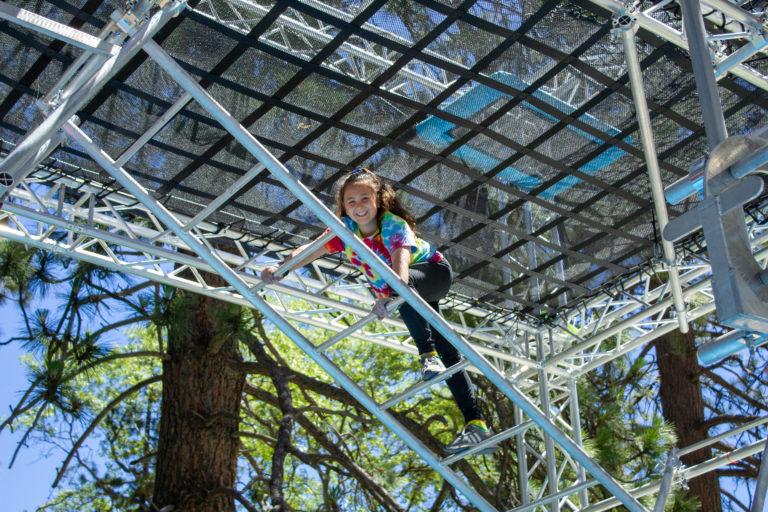 a girl traversing a metal ladder
