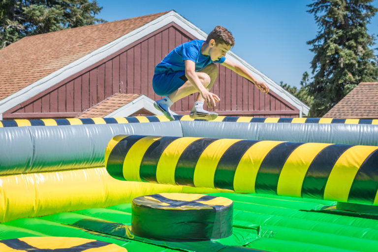 a boy jumping over a moving obstacle