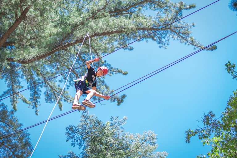 a boy walking on a ropes course