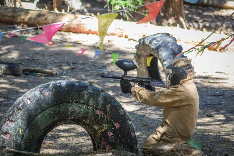 a girl taking cover while shooting a paint ball gun