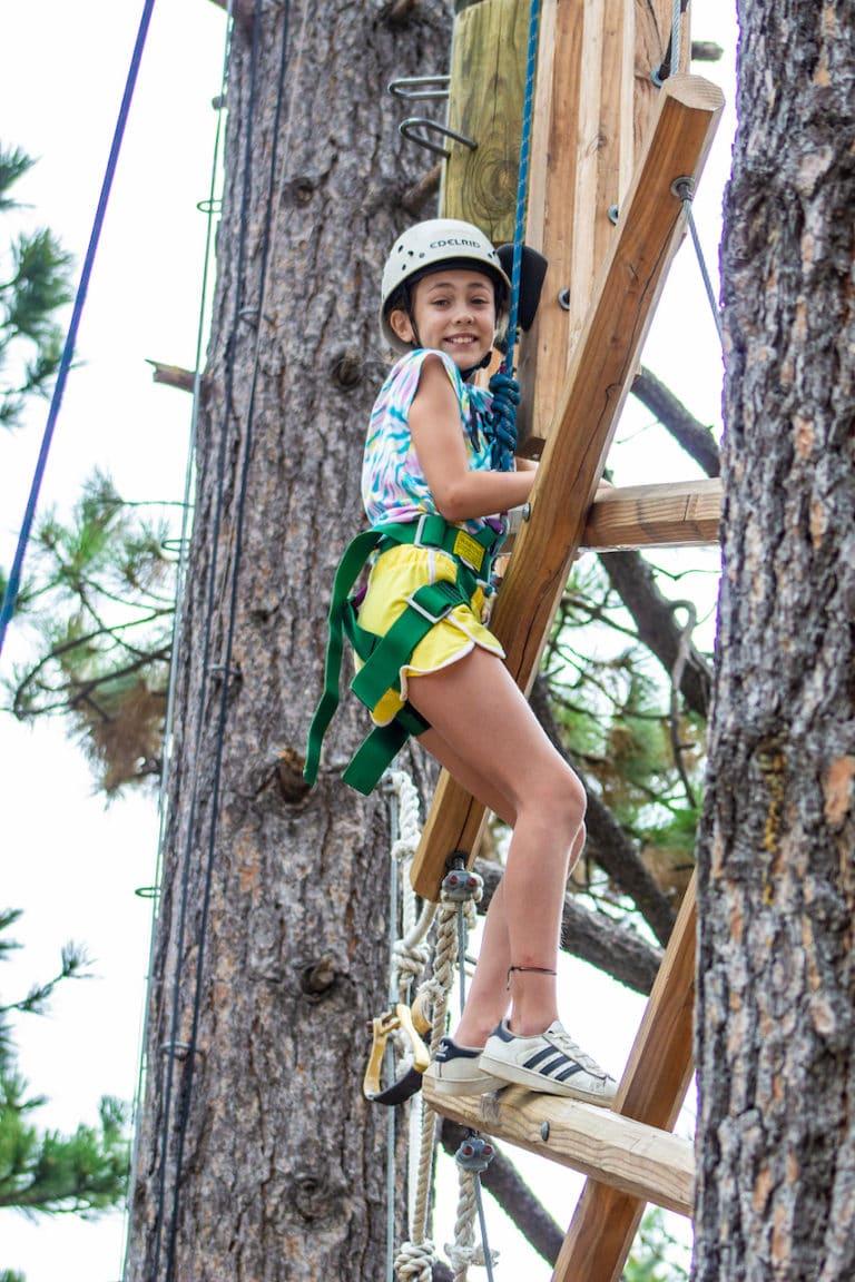 girl tree climbing at summer camp