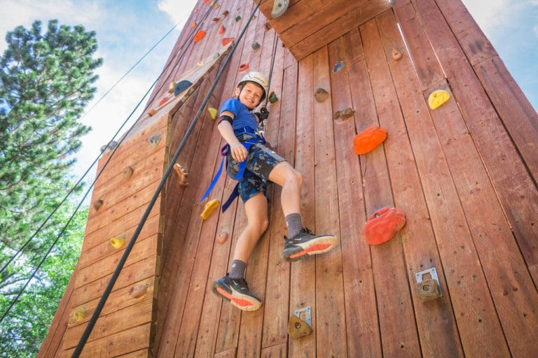 boy rock climbing at camp