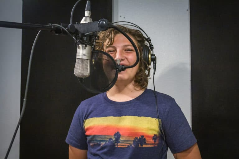 boy in recording booth at camp