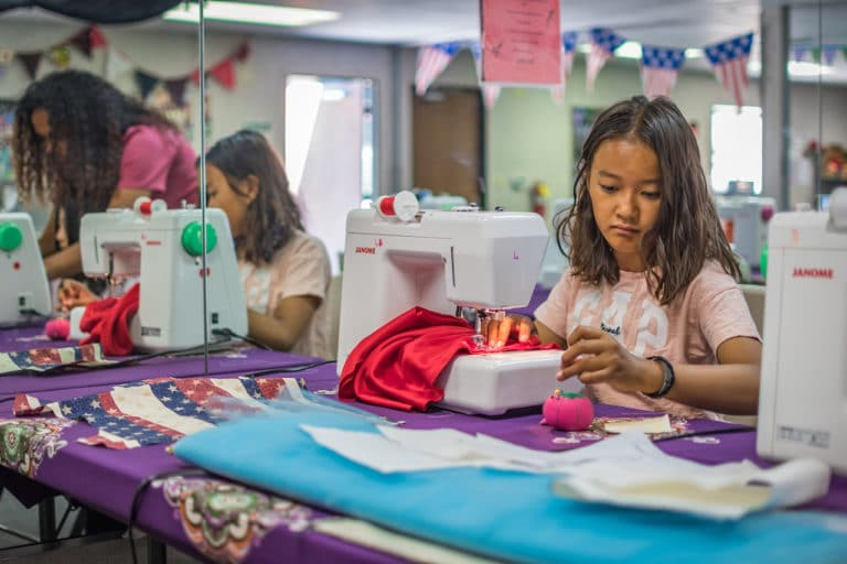 girl sitting at sewing machine at camp
