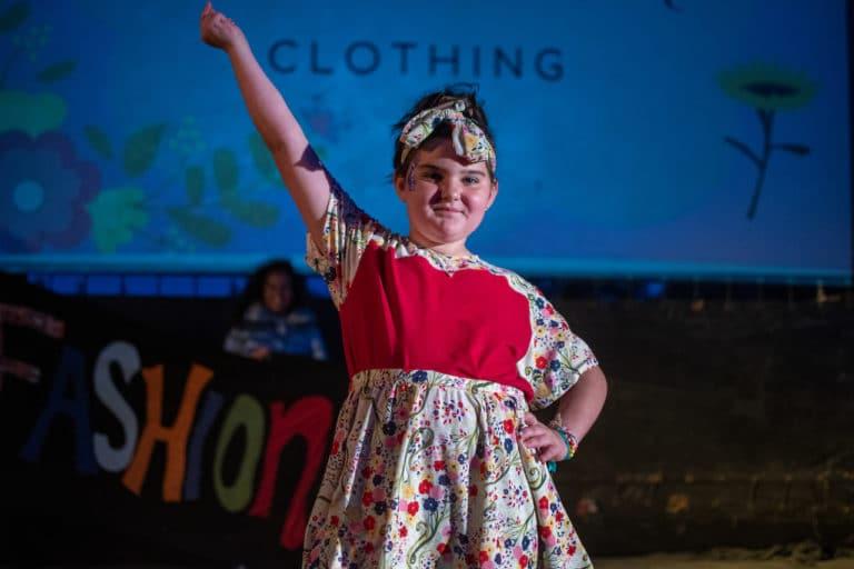girl walking modeling dress at fashion show at camp